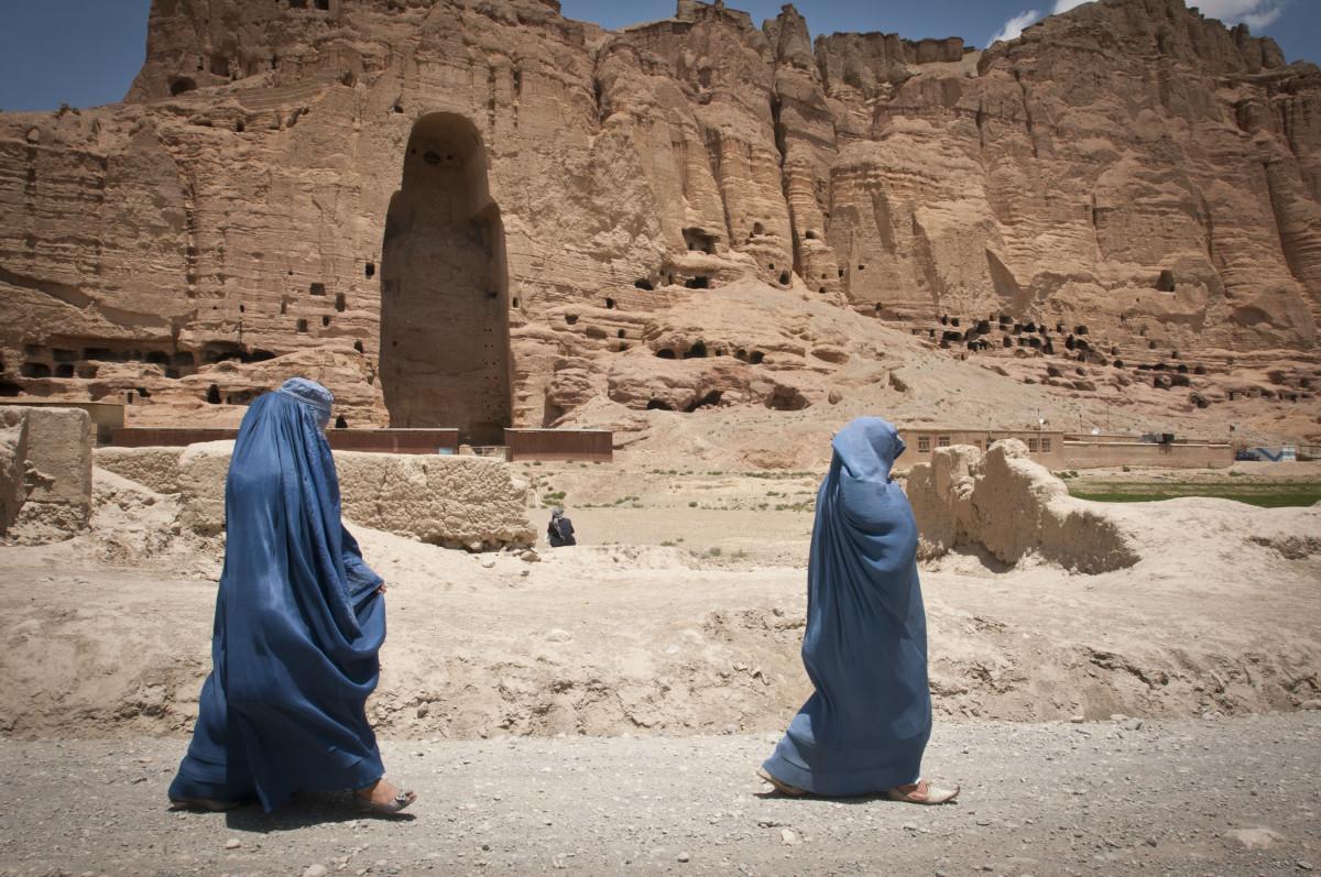 Deux femmes passent en burqa devant l'emplacement d'un des Bouddhas de Dâmiyân dynamités par les Talibans en 2001.
